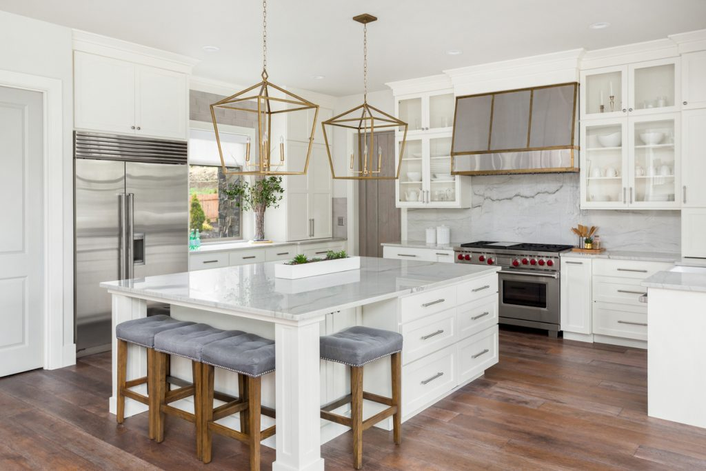 beautiful kitchen in new luxury home with island, pendant lights, and hardwood floors