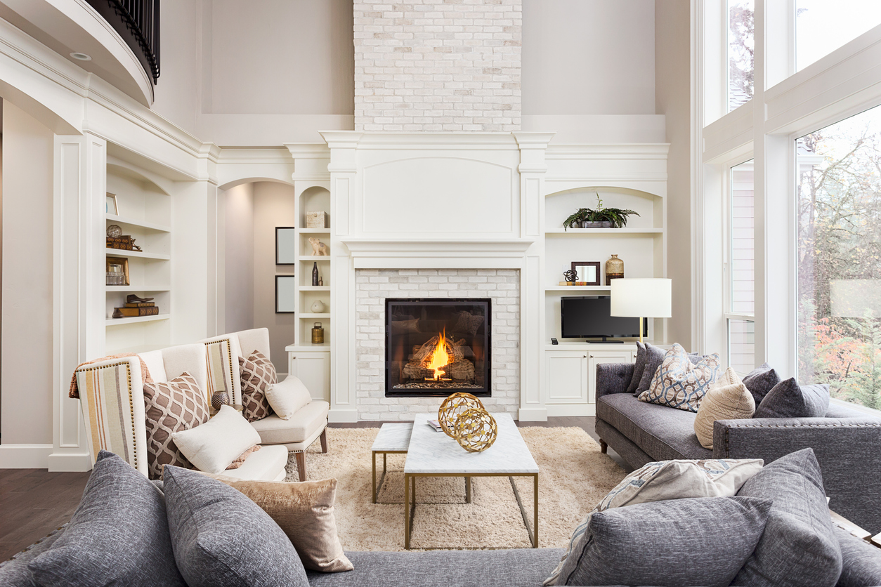 Beautiful living room interior with tall vaulted ceiling, loft area, hardwood floors and fireplace in new luxury home. Has large bank of windows